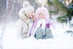 Familia feliz que se sienta en invierno al aire libre de la nieve Imagen de archivo