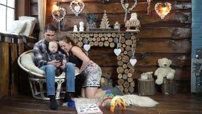 Familia feliz que se sienta en las fotos de repaso de la chimenea en su teléfono almacen de metraje de vídeo