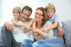 Familia feliz que se sienta en las lentes que llevan del sofá Fotos de archivo