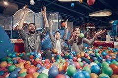 Familia feliz que se sienta en piscina con las bolas imagen de archivo