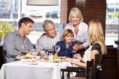Familia feliz que se sienta en restaurante Fotos de archivo libres de regalías
