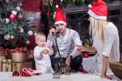 Familia feliz que se sienta en sitio festivo de la Navidad foto de archivo