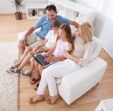 Familia feliz que se sienta en un sofá usando la computadora portátil Fotos de archivo libres de regalías