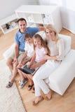 Familia feliz que se sienta en un sofá usando la computadora portátil Foto de archivo libre de regalías