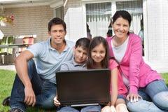 Familia feliz que se sienta junto con la computadora portátil Imagenes de archivo