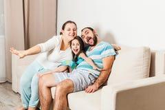 Familia feliz que se sienta junto en un sofá en la sala de estar foto de archivo libre de regalías