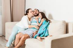 Familia feliz que se sienta junto en un sofá en la sala de estar fotos de archivo libres de regalías