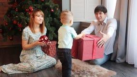 Familia feliz que se sienta por el árbol de navidad almacen de metraje de vídeo