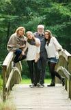 Familia feliz que se une en un puente en el bosque Imagen de archivo libre de regalías