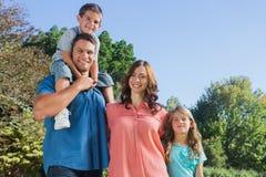 Familia feliz que sonríe en la cámara en el parque Imagen de archivo libre de regalías