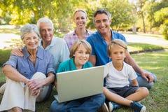 Familia feliz que sonríe en la cámara y que usa el ordenador portátil en el parque Fotos de archivo libres de regalías