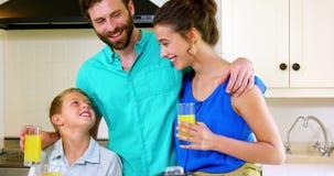 Familia feliz que sostiene el zumo de naranja metrajes