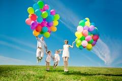 Familia feliz que sostiene los globos coloridos al aire libre. Mamá, ded y dos imagen de archivo