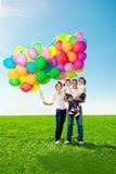 Familia feliz que sostiene los globos coloridos. Mamá, ded y daughte dos foto de archivo libre de regalías