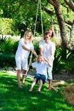 Familia feliz que tiene balanceo de la diversión Fotos de archivo