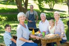 Familia feliz que tiene comida campestre en el parque Fotos de archivo libres de regalías