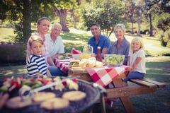 Familia feliz que tiene comida campestre en el parque Fotos de archivo