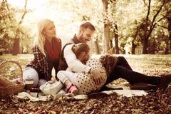 Familia feliz que tiene comida campestre en naturaleza imagenes de archivo
