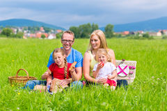Familia feliz que tiene comida campestre en prado Fotografía de archivo