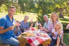 Familia feliz que tiene comida campestre y que sostiene la bandera americana Imagen de archivo libre de regalías