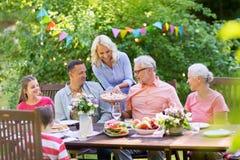 Familia feliz que tiene la cena o la fiesta de jardín del verano fotos de archivo