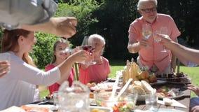 Familia feliz que tiene la cena o la fiesta de jardín del verano almacen de video