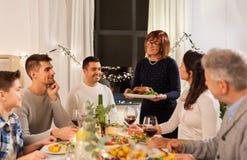 Familia feliz que tiene partido de cena en casa imagenes de archivo