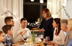 Familia feliz que tiene partido de cena en casa fotografía de archivo