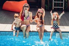 Familia feliz que tiene tiempo de la diversión en el lado de la piscina fotos de archivo