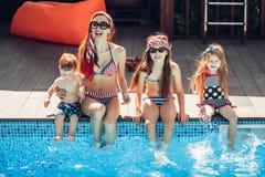 Familia feliz que tiene tiempo de la diversión en el lado de la piscina imagen de archivo