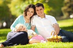 Familia feliz que tiene una comida campestre en el jardín Imágenes de archivo libres de regalías
