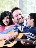 Familia feliz que toca la guitarra foto de archivo libre de regalías