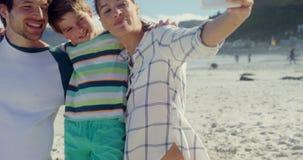 Familia feliz que toma el selfie del teléfono móvil en la playa metrajes