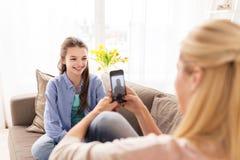 Familia feliz que toma la foto por smartphone en casa Imágenes de archivo libres de regalías