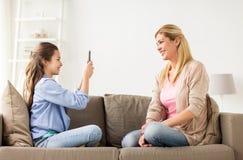 Familia feliz que toma la foto por smartphone en casa Fotografía de archivo