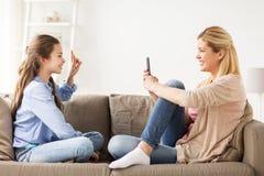 Familia feliz que toma la foto por smartphone en casa Imagen de archivo