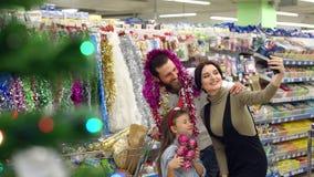 Familia feliz que toma un selfie en el supermercado con los regalos de la Navidad almacen de video