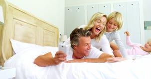 Familia feliz que toma un selfie en el teléfono móvil en el cuarto 4k de la cama metrajes