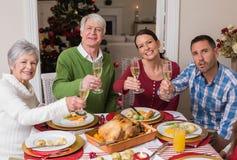 Familia feliz que tuesta en la cámara durante cena de la Navidad Fotografía de archivo libre de regalías