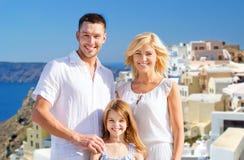Familia feliz sobre fondo de la isla del santorini Fotografía de archivo libre de regalías