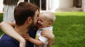 Familia feliz, sonriente La madre, padre, pequeño hijo se está abrazando Madre que besa el niño pequeño y a su marido almacen de video