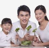 Familia feliz sonriente que se sienta en la tabla que comparte una ensalada fuera de un cuenco, tiro del estudio Fotos de archivo libres de regalías