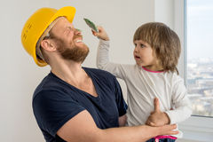 Familia feliz, trabajador de construcción en casco y pequeño niño Fotografía de archivo libre de regalías
