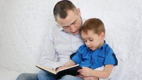 Familia feliz: un padre y su hijo están leyendo un libro interesante almacen de video
