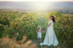 Familia feliz: una mujer embarazada hermosa joven con su pequeña hija linda que camina en el campo anaranjado del trigo en a imagenes de archivo