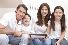 Familia feliz usando el ordenador de la tablilla en el país Imagen de archivo libre de regalías
