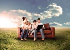 Familia feliz usando el ordenador portátil en un campo imagen de archivo libre de regalías
