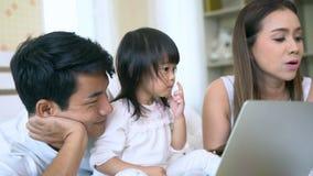 Familia feliz usando la computadora portátil junto
