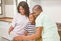 Familia feliz usando la computadora portátil Fotografía de archivo