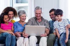 Familia feliz usando la computadora portátil en el sofá Imagen de archivo libre de regalías